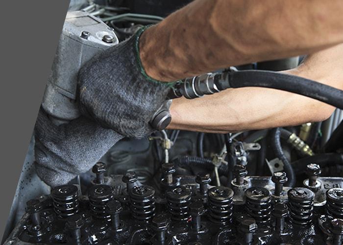 man repairing diesel engine