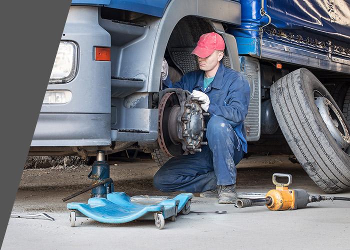 man repairing semi truck truck