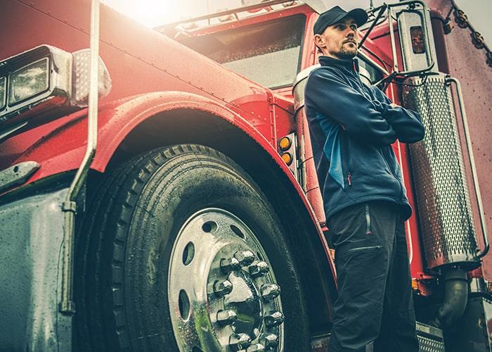 man standing next to semi truck waiting on repair